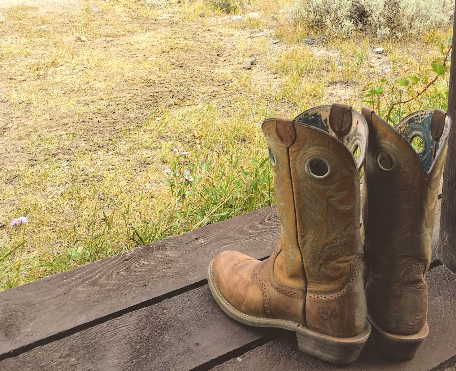 Pair of tan cowboy boots sitting on porch